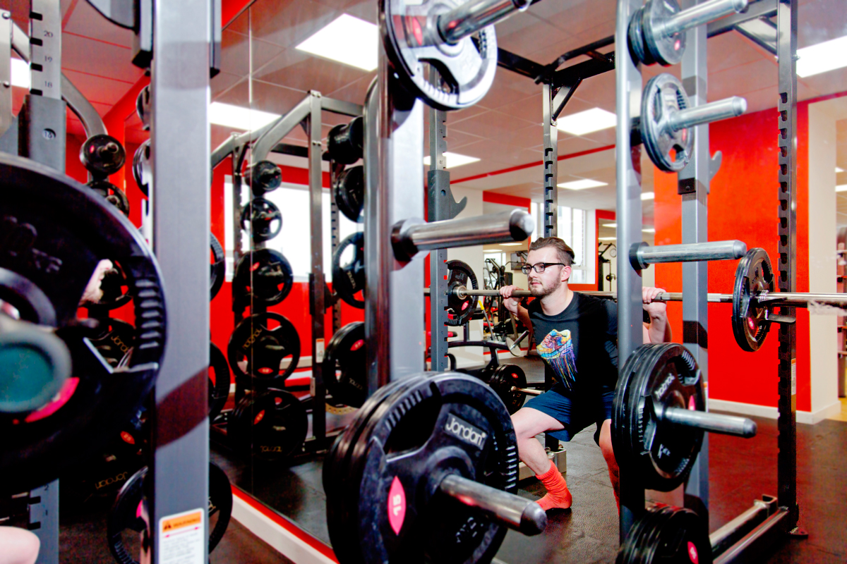 A student uses the weights in the fitness centre