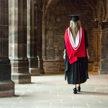 Graduate in gown walking in the Cathedral corridor