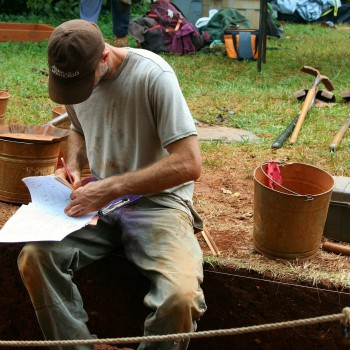 Student documenting an archaeology dig finds