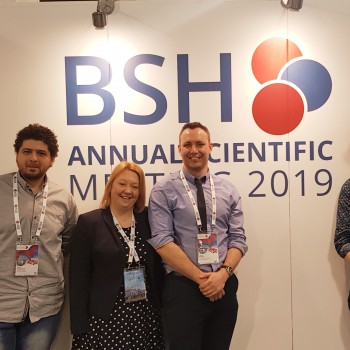 Four people standing in front of a wall with BSH Annual Scientific Meeting 2019 on it