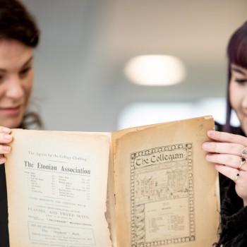 Photo of Alumni team reading college magazine