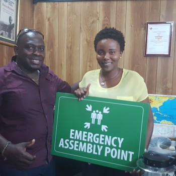 Dr Servel Miller presenting Emergency Assembly Point signs to Martina Medley, Parish Disaster Coordinator, St Thomas Parish Council in Jamaica.