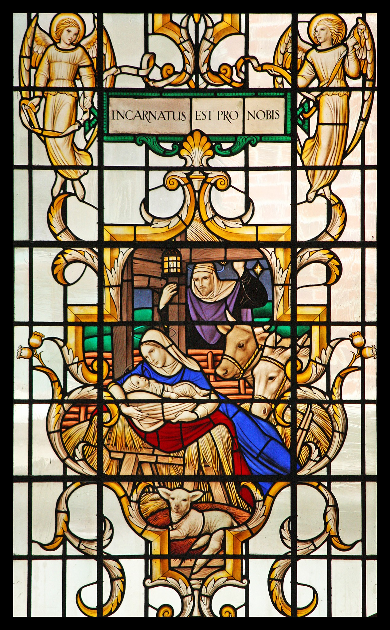 Stained glass window showing the birth of Christ, surrounded by Mary and Jesus, and a cow, donkey and lamb, with the text 'incarnatus est pro nobilis'