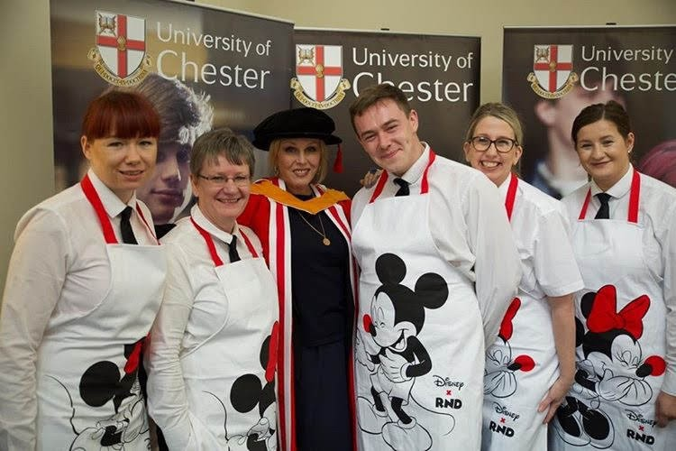 Joanna Lumley with catering staff in Comic Relief aprons