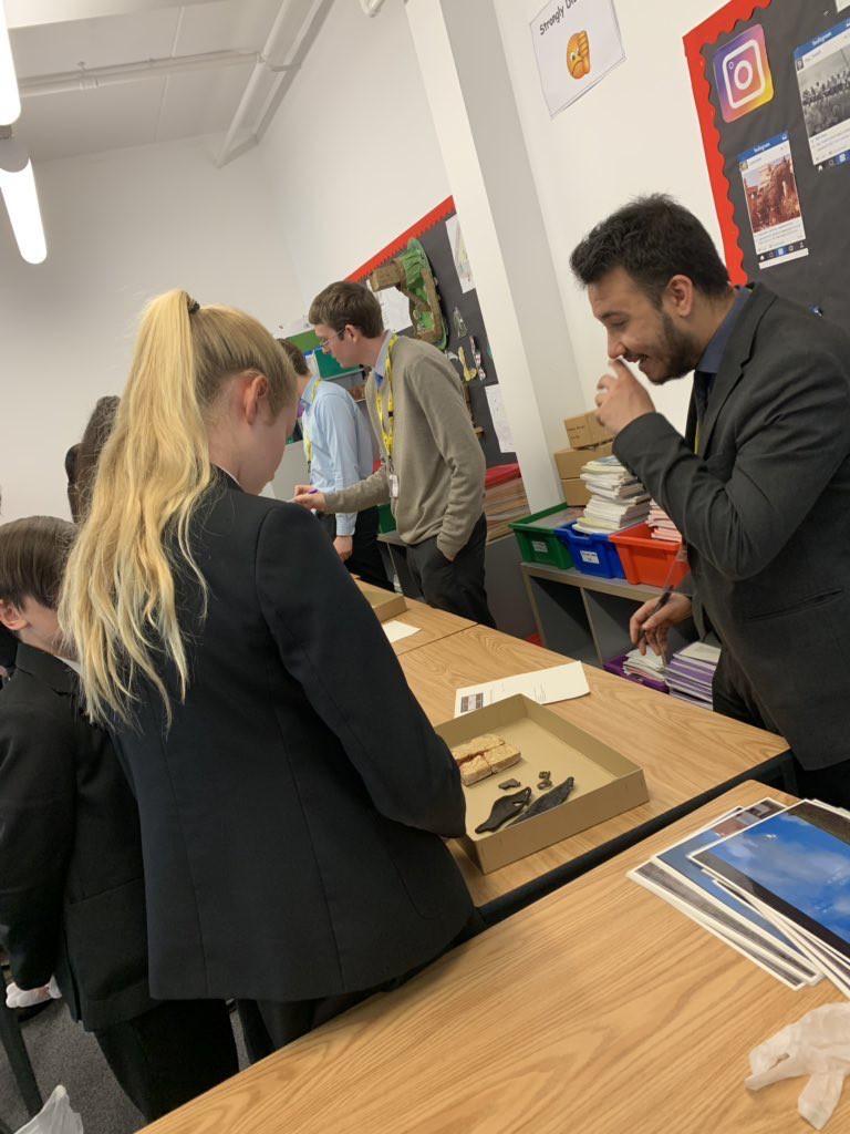 Students at Neston High School examining a medieval tile, keys, pilgrim badge and shoe.