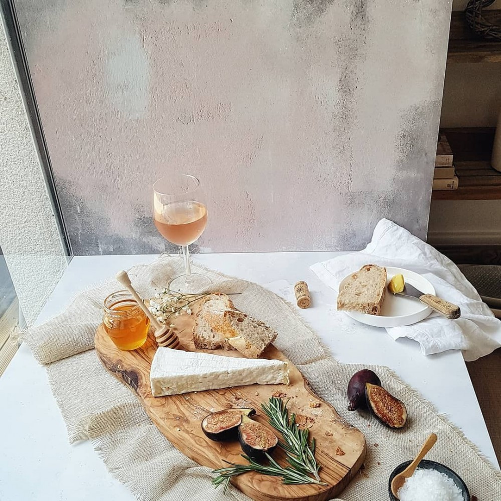A platter of Brie, figs, bread and honey on a wooden board.